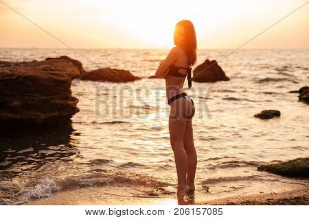 Back view of happy brunette woman in bikini posing near the sea and looking at the camera