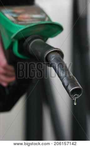 Drop of fuel drips from petrol pistol