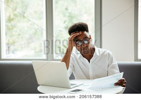 Picture of concentrated serious young african man sitting coworking by laptop computer near documents. Looking aside.