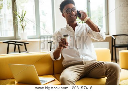Picture of handsome young african man sitting coworking by laptop computer. Looking aside talking by phone drinking coffee.