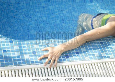 Sexy slim young lady by swimming pool in gstring bikini swimwear.