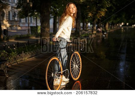 Back view of smiling brunette woman in autumn clothes standing in park with bicycle and looking at the camera