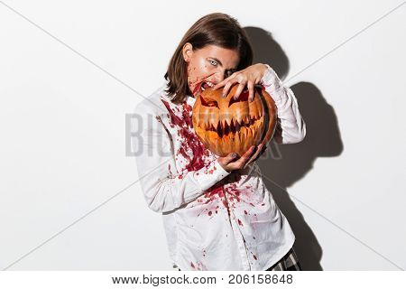 Mad terrifying zombie woman covered in blood stains holding a halloween pumpkin isolated over white background