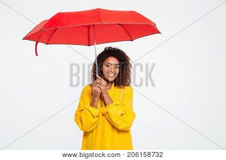 Picture of smiling african woman in raincoat hiding under umbrella and looking at the camera over white background
