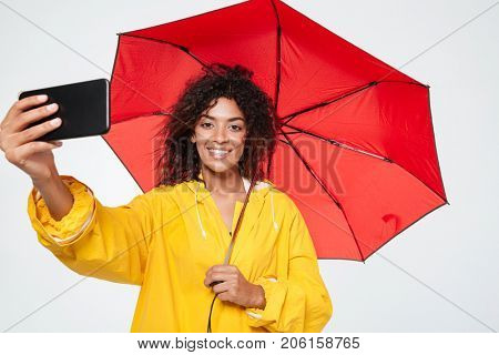Smiling african woman in raincoat hiding under umbrella and making selfie on her smartphone over white background