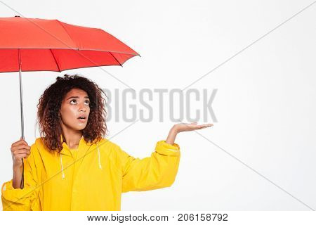 Picture of confused african woman in raincoat hiding under umbrella and waiting rain over white background