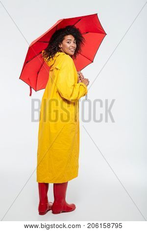 Full length back view image of smiling african woman hiding under umbrella and looking at the camera over white background