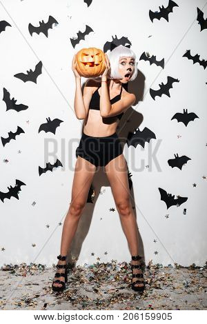 Picture of pretty young woman in halloween costume cat on party over white background with pumpkin. Looking camera.