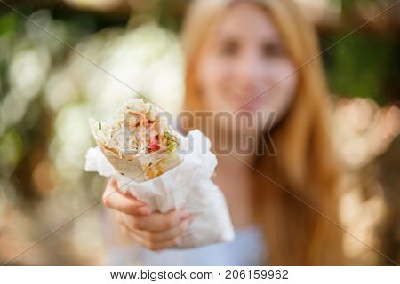 Pretty sunny girl holding juicy chicken shawarma on the nature. Close-up of fast food outdoors.