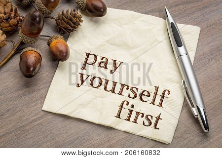Pay yourself first - financial advice, handwriting on a napkin with acorn and cone decoration