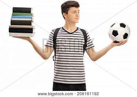 Indecisive teenage student holding a football and a stack of books isolated on white background