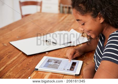 Teenage Girl With Digital Tablet Revising For Exam At Home