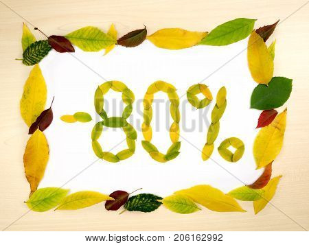 Word 80 percent made of autumn leaves inside of frame of autumn leaves on wood background. Eighty percent sale. Autumn sale template