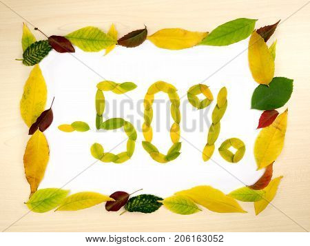 Word 50 percent made of autumn leaves inside of frame of autumn leaves on wood background. Fifty percent sale. Autumn sale template