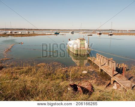 Parked Boat In Estuary With Wooden Walkway To