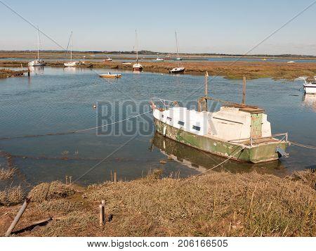 Moored Boat In Estuary River Stream Tollesbury Essex Marsh Land Scene