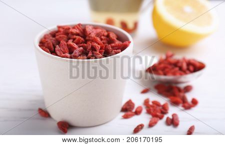 Cup with dried goji berries on table
