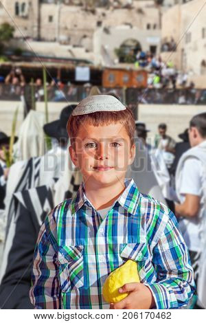 Autumn Jewish holiday Sukkot. Beautiful Jewish boy in white skullcap, with etrog. People in white Taliths pray at the Western Wall of the Temple