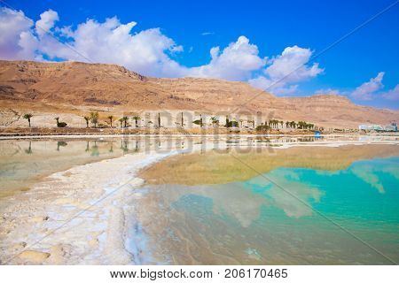 Therapeutic Dead Sea, Israel. Between the sea and dry mountains of red sandstone highway passes. The concept of medical and ecological tourism
