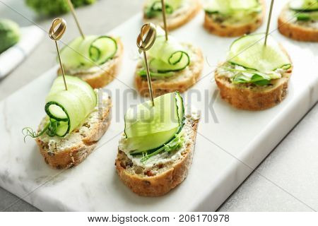 Set of delicious canapes with fresh cucumber on board