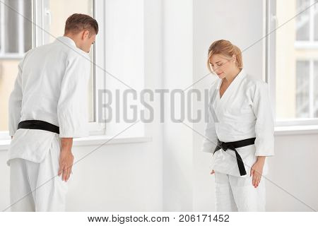 Young man and woman performing ritual bow prior to practicing karate in dojo