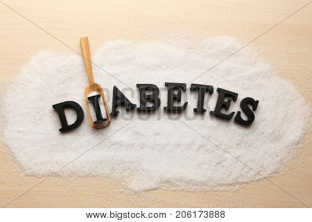 Composition with word Diabetes, sugar and wooden scoop on light background