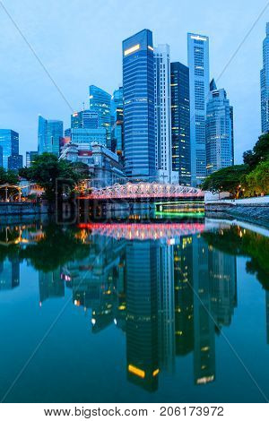 Singapore downtown financial business district skyline at dawn with brightly lit Anderson Bridge in the middle and reflections off the calm Singapore River.