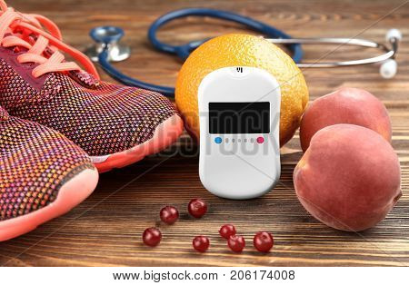 Composition with digital glucometer, fruits and sneakers on wooden background. Diabetes concept