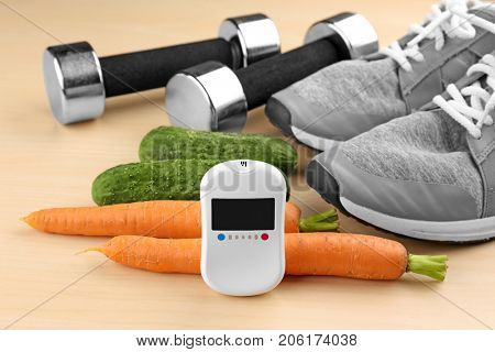 Composition with digital glucometer, vegetables and sport inventory on light background. Diabetes concept