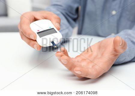 Man using digital glucometer indoors. Diabetes concept