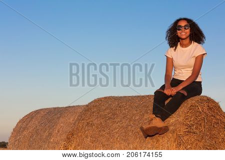 Outdoor portrait of beautiful happy mixed race African American girl teenager female young woman smiling laughing with perfect teeth and sunglasses sitting on hay bale in golden evening sunshine