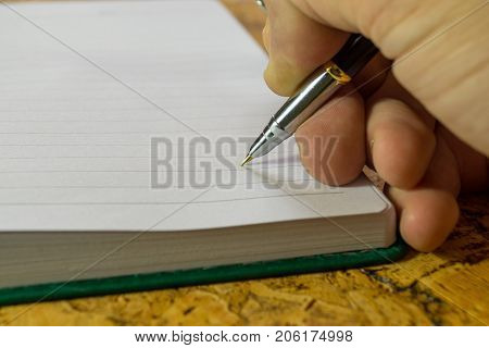The human hand with a pen writing notes in a diary.