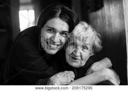 Elderly woman in an embrace with his adult daughter. Black and white portrait.