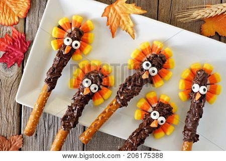 Thanksgiving Candy Corn Turkey Pretzel Rods On A White Plate, Overhead Scene