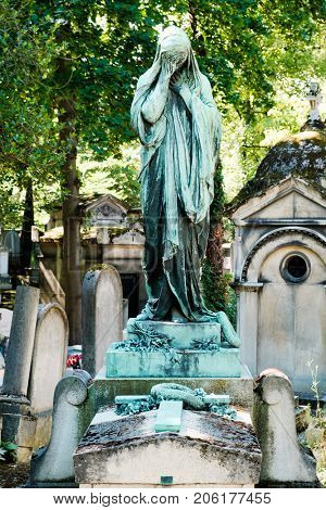 Statue of a weeping young woman at the Pere Lachaise cemetery in Paris