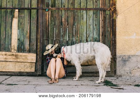Country girl relaxing at barn door with her dog.