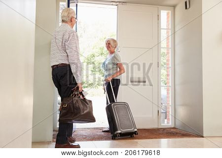 Senior couple with luggage leaving home for a holiday