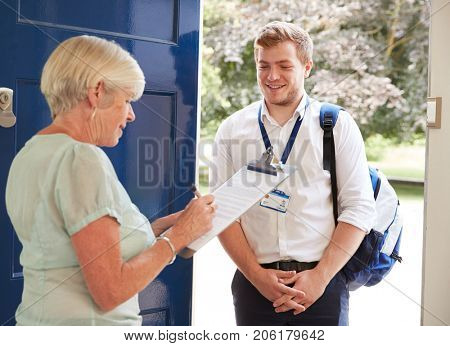 Senior woman filling in survey for visitor at her front door