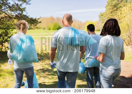 volunteering, people and ecology concept - group of volunteers with garbage bags walking after cleaning park area