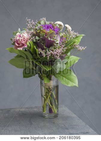 Bouquet Of Flowers Pink Violet And Green With Decorative Cabbage In Glass Vase On Abstract Grey Back