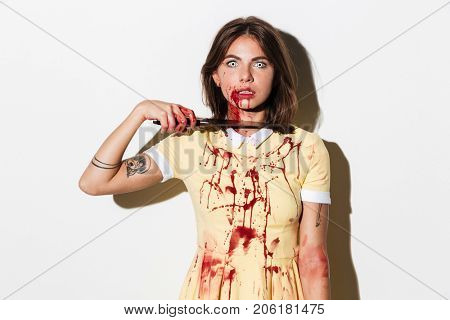 Mad creepy zombie woman cutting her throat with a knife and looking at camera isolated over white background
