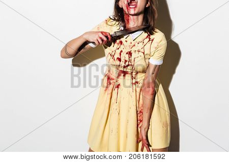 Cropped image of a zombie woman bleeding and injured holding a knife at her throat isolated over white background