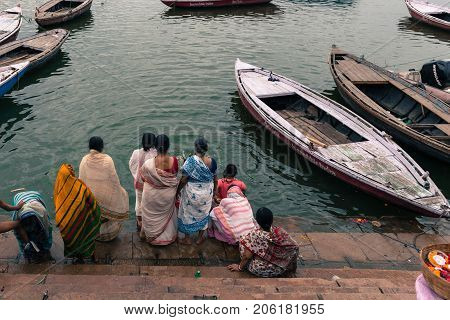 VARANASI INDIA - MARCH 13 2016: Wide angle picture of indian people bathing and docked boats at the holy Ganges River in the city of Varanasi in India