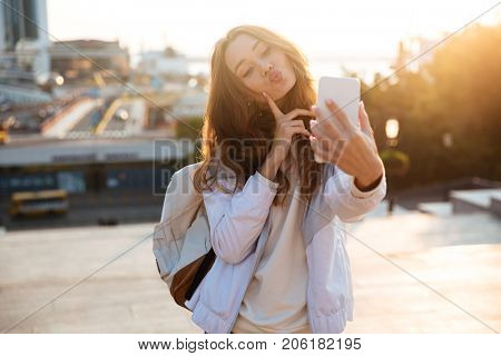 Pretty brunette woman in autumn clothes making selfie on smartphone and showing grimace outdoors