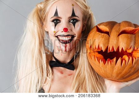 Close up of a crazy smiling blonde woman in halloween clown make-up and blood streaks holding curved pumpkin and looking at camera isolated over gray background
