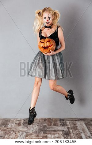 Full length portrait of a scary crazy blonde woman in halloween clown make-up and blood streaks holding curved pumpkin and jumping isolated over gray background