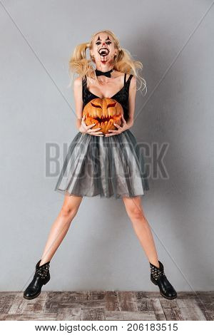 Full length portrait of a laughing crazy blonde woman in halloween clown make-up and blood streaks holding curved pumpkin and jumping isolated over gray background
