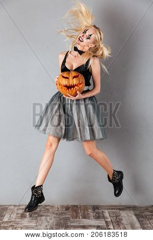 Full length portrait of a smiling crazy blonde woman in halloween clown make-up and blood streaks holding curved pumpkin and jumping isolated over gray background