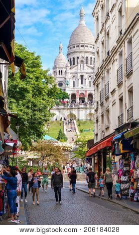 PARIS,FRANCE - AUGUST 4, 2017 : Street scene in Montmartre with the Sacre Coeur Basilica on the background