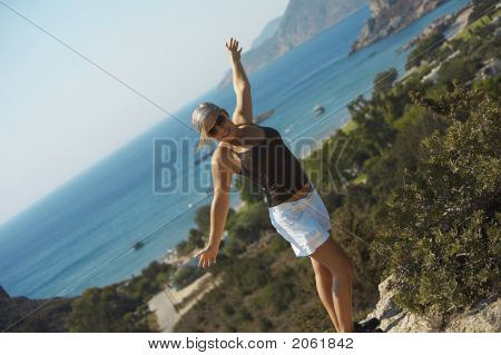 A Young Woman Is Standing On A Cliff